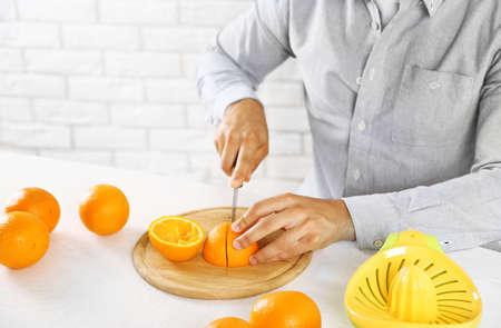 Young man cutting oranges, preparing orange juice