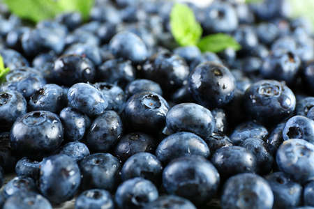 Tasty ripe blueberries with green leaves close up