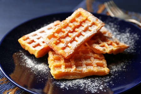 Sweet homemade waffles on plate, on dark wooden background