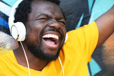 African American man listening music with headphones near graffiti wall outdoors Stock Photo