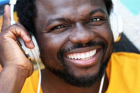 African American man listening music with headphones near graffiti wall outdoors Stock Photo