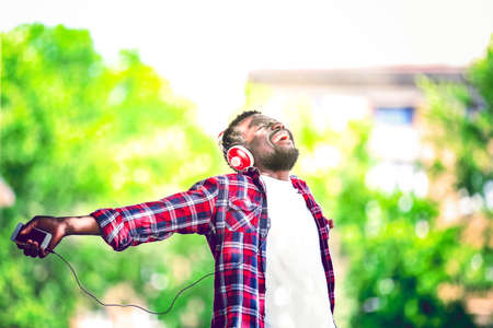 African American man listening music with headphones outdoors