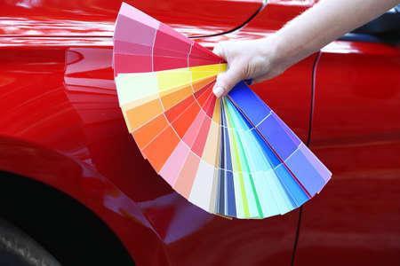 赤い車の背景の上に色のサンプルを持つ女性の手 写真素材