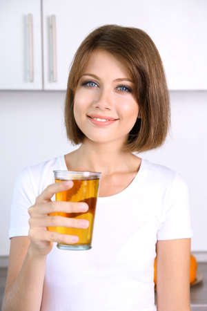 Young beautiful woman showing glass of apple juice