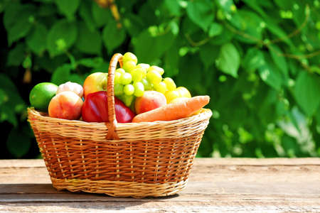 Heap of fresh fruits and vegetables in basket on table outdoors Stock Photo