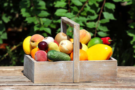 Heap of fresh fruits and vegetables in crate on table outdoors Stock Photo