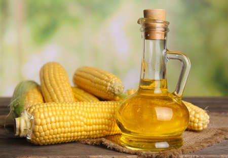 Bottle of oil with fresh corn on bright background Stock Photo
