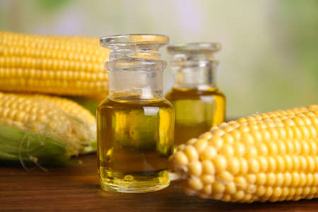 Fresh corn with bottles of oil on bright background Stock Photo