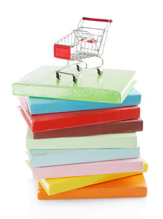 Stack of colorful books with small shopping cart isolated on white Stock Photo