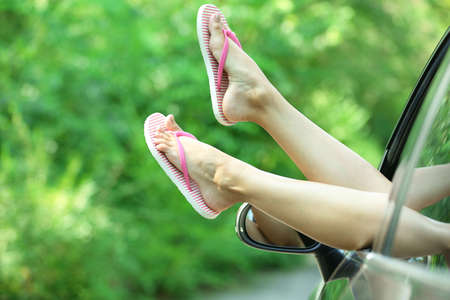 Female legs out car window on nature background
