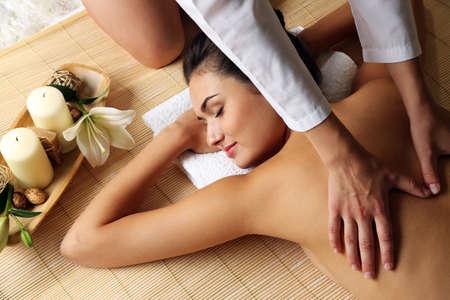 Young woman enjoying back massage in beauty spa salon Stock Photo
