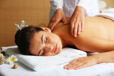 Young woman on massage table in beauty spa salon Stock Photo
