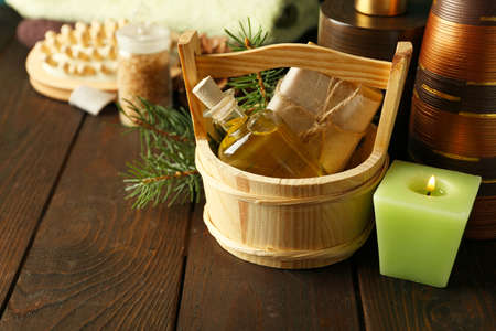 Essential oil of pine, handmade soap in wooden bucket and spa treatments on wooden background Stock Photo