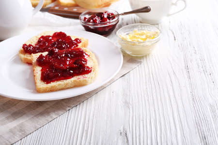 Bread with butter and homemade jam in plate on wooden background