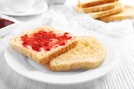 Bread with homemade jam in plate on wooden table, closeup