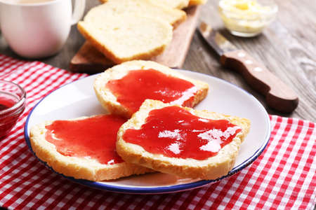 Bread with butter and homemade jam in white plate on red checkered napkin, closeup