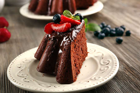 Piece of chocolate cake with berries in plate on table, closeup