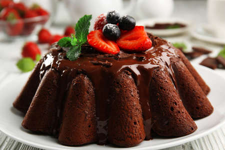 Delicious chocolate cake with berries in plate on table, closeup