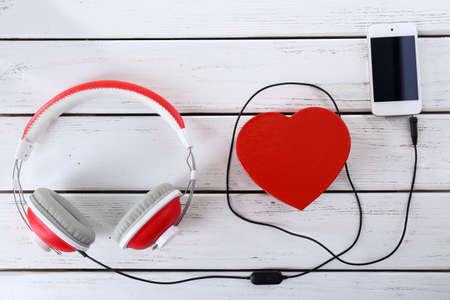 headphones with heart and phone on wooden background Stock Photo