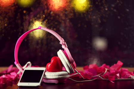 Decorative heart with headphones and mobile phone on lights background 版權商用圖片
