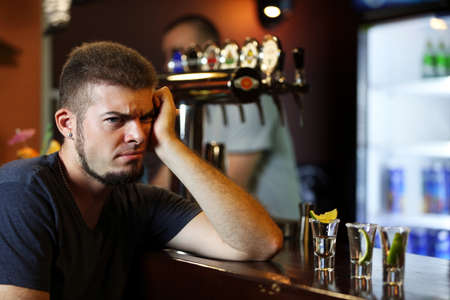 Young drunk man drinking tequila in bar