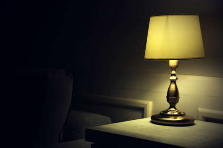 Old fashion table lamp on nightstand on wall background