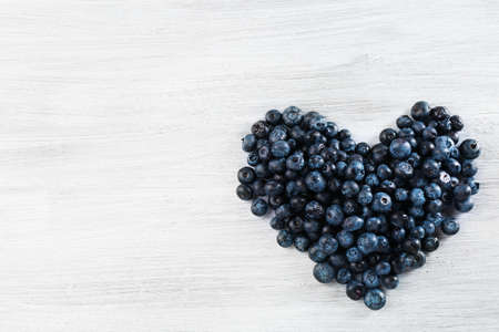 Heart of blueberries on wooden background Фото со стока