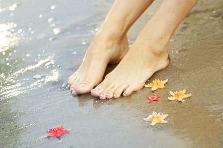 Weibliche Beine mit Meereswellen am Sandstrand