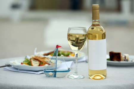 Bottle of luxury wine with tasty salad on white served table Stock Photo