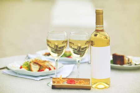 Fles luxewijn met smakelijke salade op witte gediende lijst