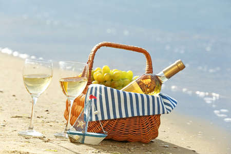 Picnic basket with bottle of wine on sand beach Stock Photo