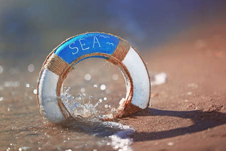 Beautiful life buoy in the sand on unfocused sea background Stock Photo