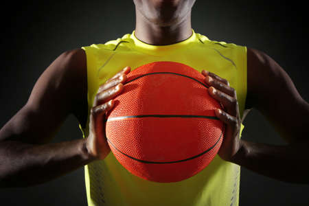 African American basketball player holding ball on dark background