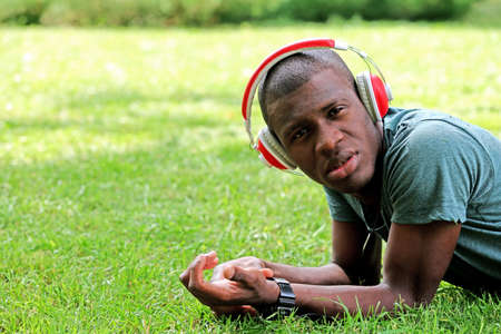 Handsome African American man with headphones lying on green grass Stock Photo