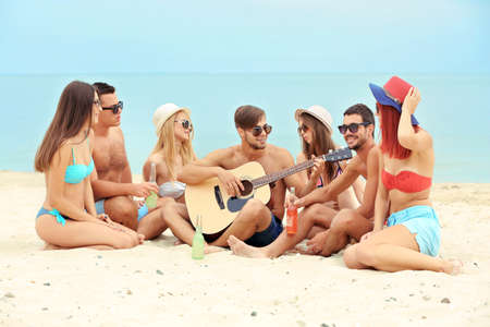 Beautiful young people with guitar having fun on beach