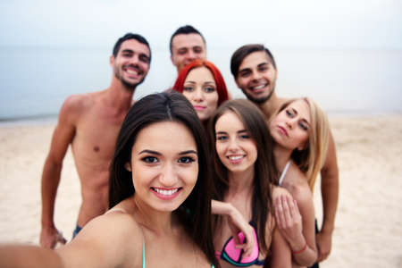 Beautiful young people making selfie on beach