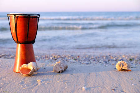 Beautiful ethnic drum with seashells on the beach on sunrise background