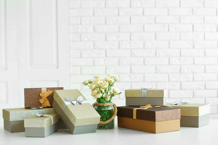 Beautiful gift boxes with bouquet of flowers on the table in front of brick wall, close up