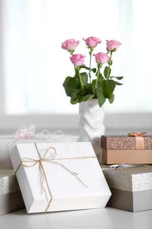 Composition of cute gift boxes and roses on white table Stock Photo