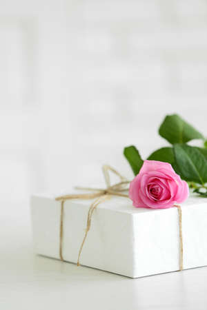 Big white gift box with rose on the table, close up Stock Photo