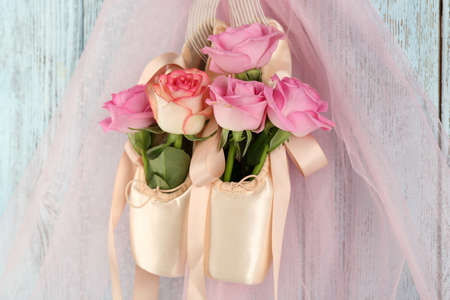 Zapatos de fútbol decoradas con rosas en él sobre fondo azul de madera Foto de archivo - 94060513