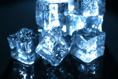 Shining ice cubes under blue light on liquid background Stock Photo