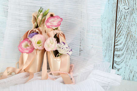 Decorated with flowers ballet shoes on satin background