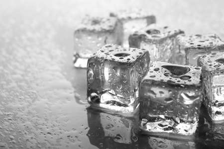Melting ice cubes with drops around, close up Stock Photo