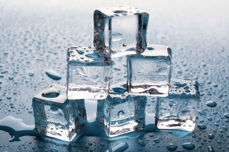 Melting ice cubes putted as pyramid with drops around, close up