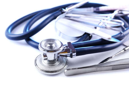 Stethoscope and surgery instruments on white background, close up