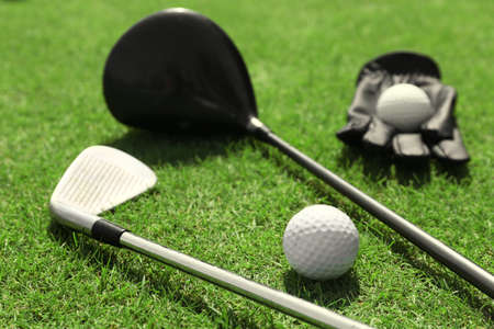 Golf clubs with ball and black glove on a green grass, close up Imagens