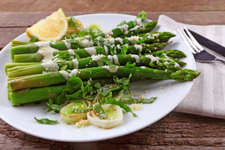 Appetizing asparagus in sour cream sauce with onion, cheese and lemon on white plate against wooden background, close up