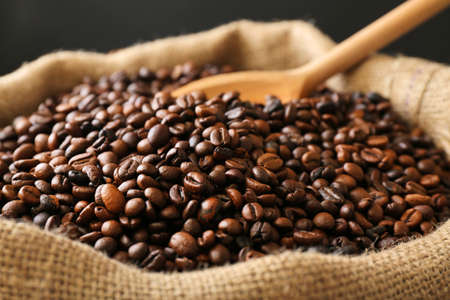 Sac with roasted coffee beans with spoon on dark background Фото со стока - 94123376