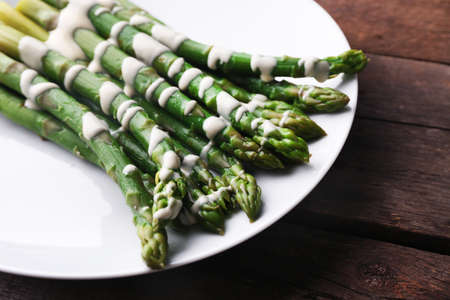 Appetizing asparagus in sour cream sauce on white plate against wooden background 版權商用圖片